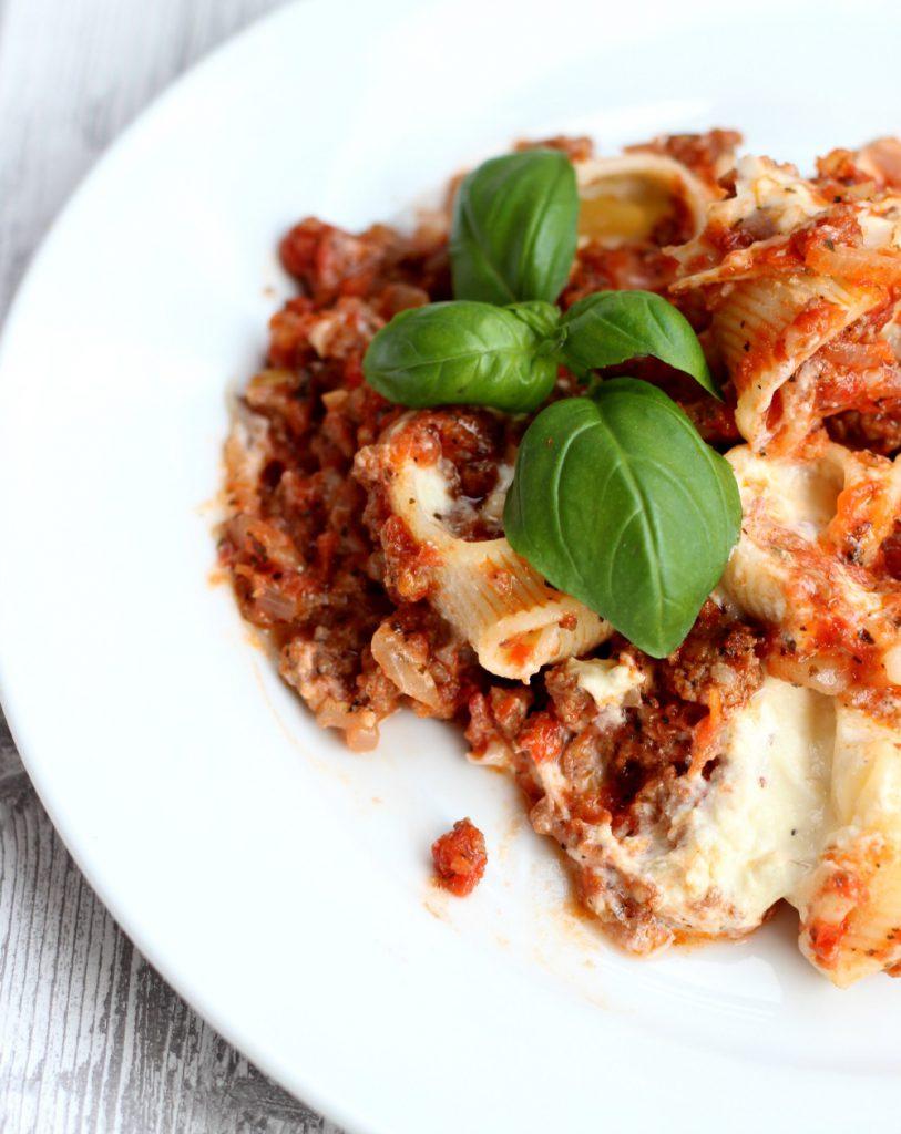 Fylte pastaskjell med kjøttsaus og basilikum.